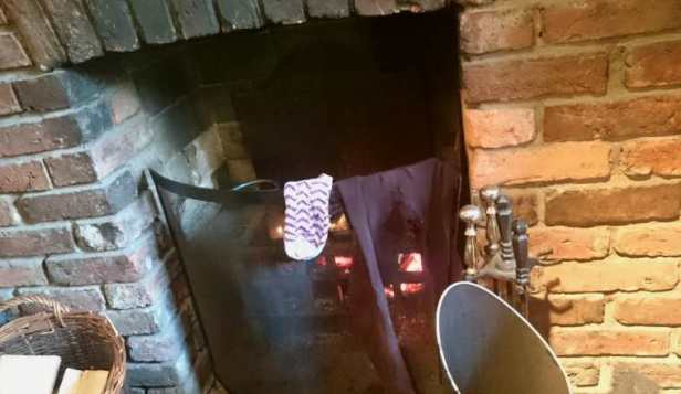 Image of open fire in brick surround with leggings and socks hanging on fireguard in front