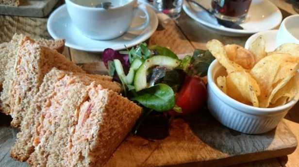 Image of plate of brown bread sandwiches with bowl of crisps on table inf ront of coffee cups