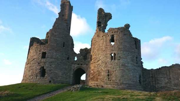 Image of ruined grey stone castle on grassy mound with two round towers either side of portcullis gate