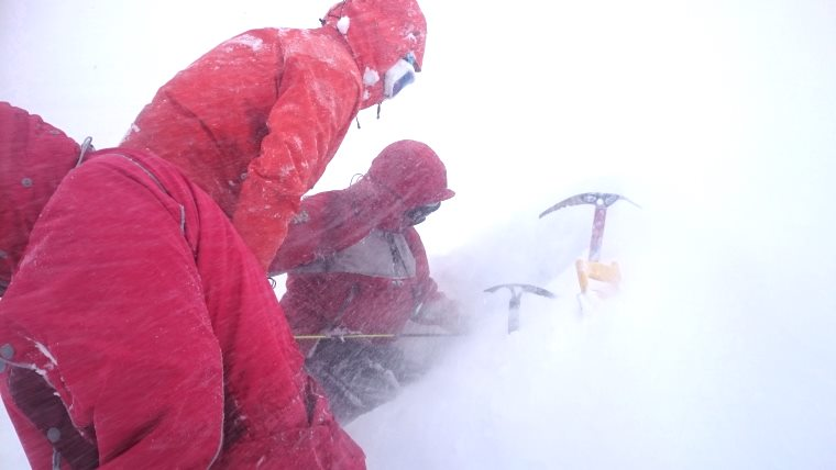Image of three people in red ski jackets digging hole in snow with 2 ice axes and a saw handle half buried in snow