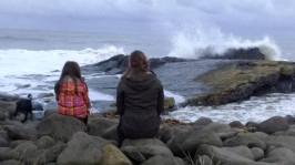 IMage of woman and girl sitting on rocks with crashing waves in front of them, grey skies and dog to left