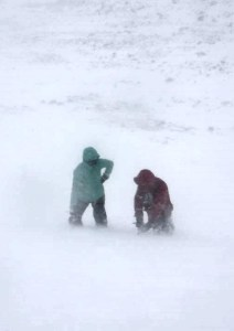 Image of woman in green jacket and man in red jacket talking at bottom of snow covered cliff 2