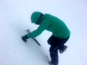 Image of woman in green ski jacket with crampons, ski goggles and ice axe climbing steep snow slope