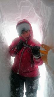Image of woman in red snow gear digging with shovel in snow hole tunnel with daylight in entrance behind