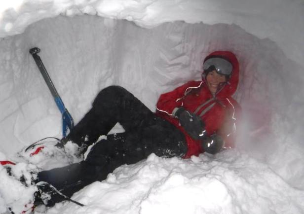 Image of woman in red snow gear lying on snow bed in snow hole with shovel in background