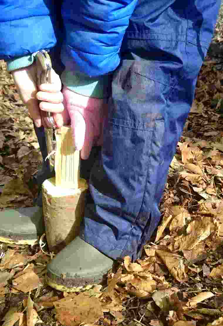 Image close up of child's hands using whittling knife on piece of wood in mallet shape held between feet in wellies on leaf litter of woodland floor