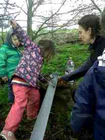 Image of child in blue jacket and pink waterproofs pulling piece of wood ona string down a drainpipe in woods