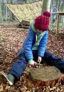 Image of child in blue outdoor gear and red bobble hat sat on a log whittling a stick in woods