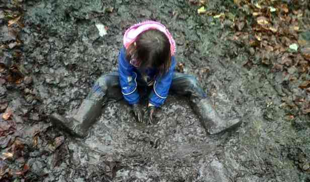 Image of child in blue splashsuit sitting in a pool of mud and leaves