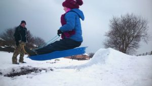 Image of girl in blue outdoor gear sitting on blue plastic sledge flying through air over snow jump with man background
