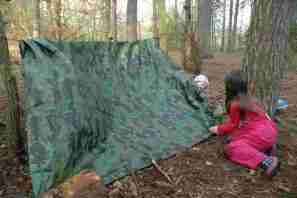 Image of two girls pegging out a camouflage tarpaulin between trees in woods