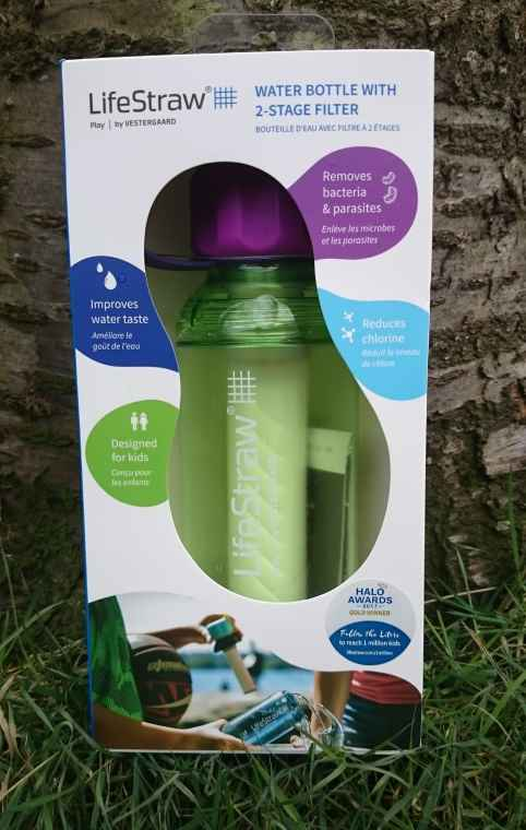 Image of white box containing green plastic Lifestraw water bottle standing on grass with tree trunk behind