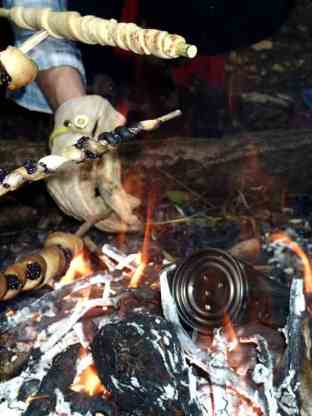 Image of white hot wood fire and flames with blackened tin can in embers and dough wound around sticks being held to cook over the flames