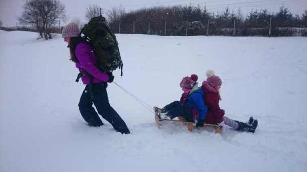 Image of woman in snow gear and huge army backpack pulling wooden sledge in deep snow with two girls in snow gear sitting back to back on sledge