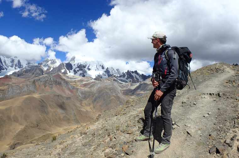 Image of mountaineer with hiking poles on mountain ridge overlooking snow capped peaks