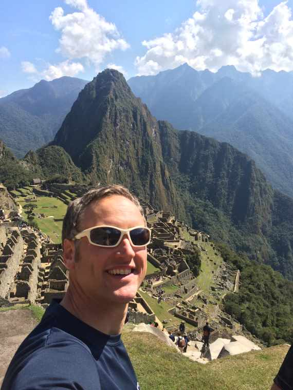 Image of selfie of man with Machu Picchu city and mountains behind