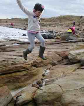 Image of girl in pale clothes leaping between rocks with arms in air on beach with sand and sea in background