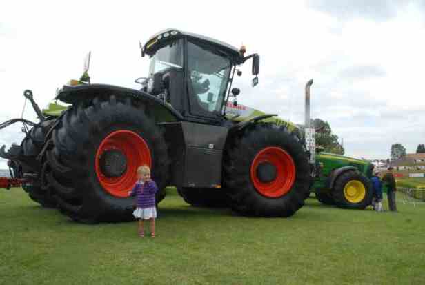 Image of tiny toddler in front of giant tractor on grass