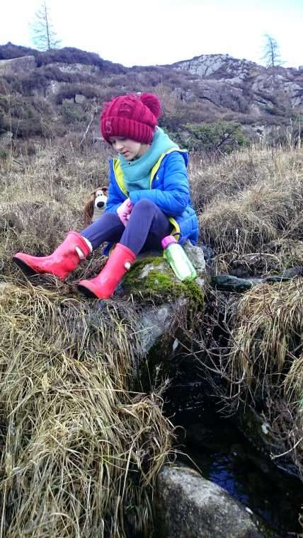 Image of girl in blue jacket sat on rocks looking down with stream below and hills behind