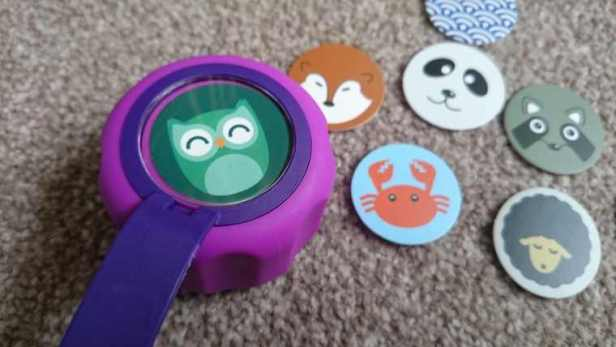 Image of purple drinking bottle cap on beige carpet with animal picture in centre and other circular animal pictures on floor