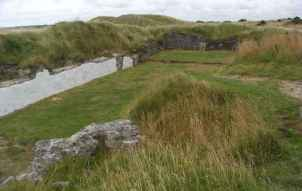 Image of ruined white walls with grass around in sand dunes with grey sky above