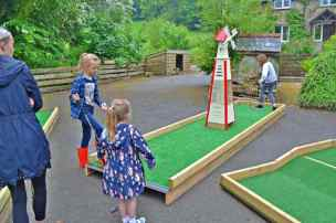 Image of children playing crazy golf course with red and white windmill in centre