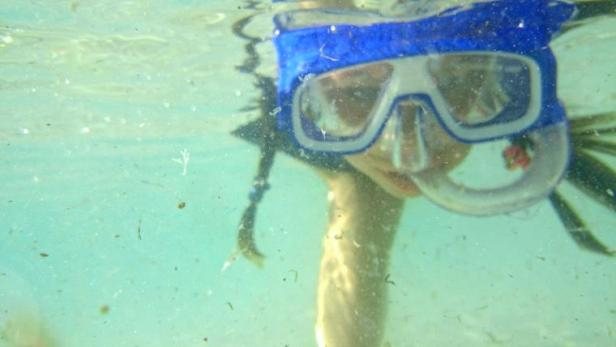 Image of close up of girl's face in snorkel mask under water