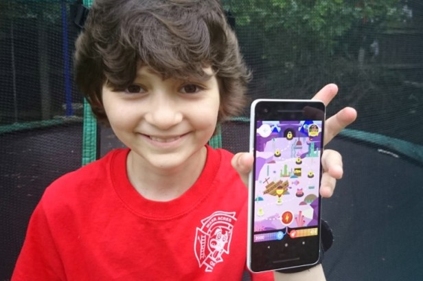 Image of girl in red T-shirt with trampoline behind holding up smart phone with bright coloured image on screen