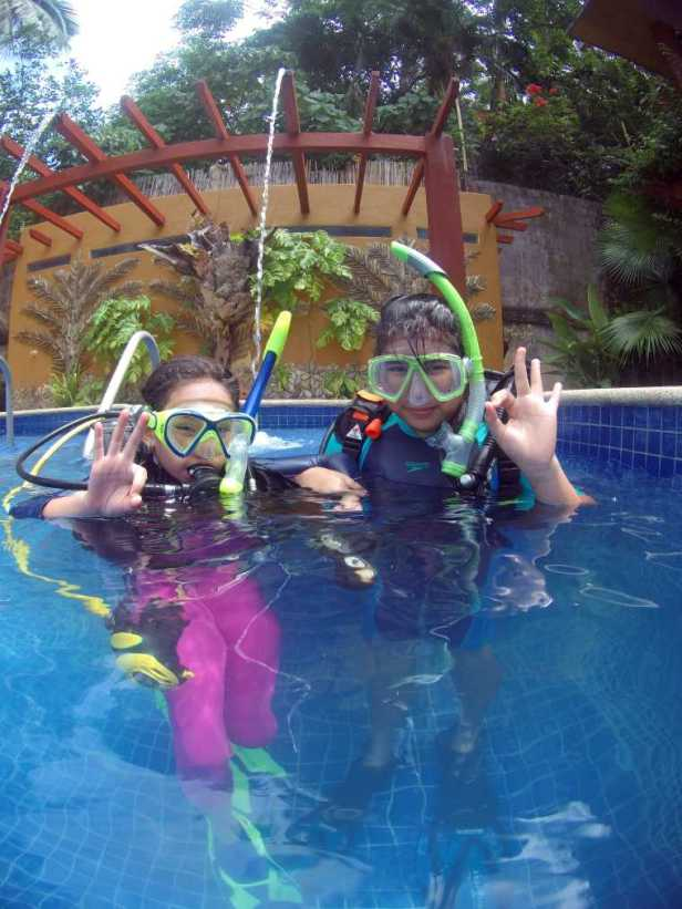 Image of two children in diving gear making OK sign with fingers in outdoor pool