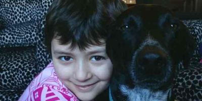 Image Of Girl In Pink Tipi Pattern Top Cuddling Black Dog