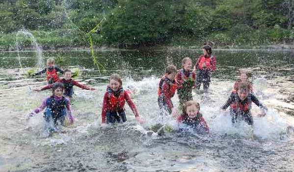 2Image of group of children wearing wetsuits in a river all making a huge splash and throwing weeds