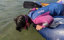 Image of girl in blue and pink Iglu wetsuit wearing goggles leaning from inflatable dinghy into sea