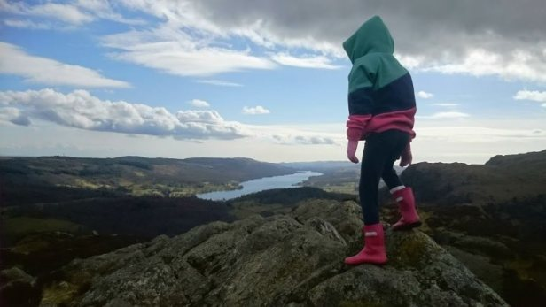 Image of child in coloured top and red wellies standing on peak of hill overlooking distant lake with hill landscape and sky behind