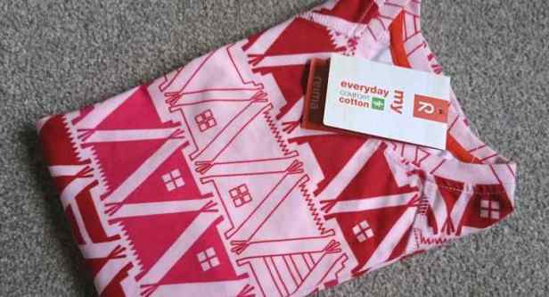 Image of folded pink and red top with tipi fabric pattern showing laberl stating Reima everyday comfort cotton