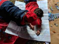 Image of 2 girls in red top and cap lying on ground looking at large paper map