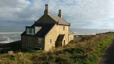 Image of detached stone house with grey tiled roof on cliffs with sea and sky behind