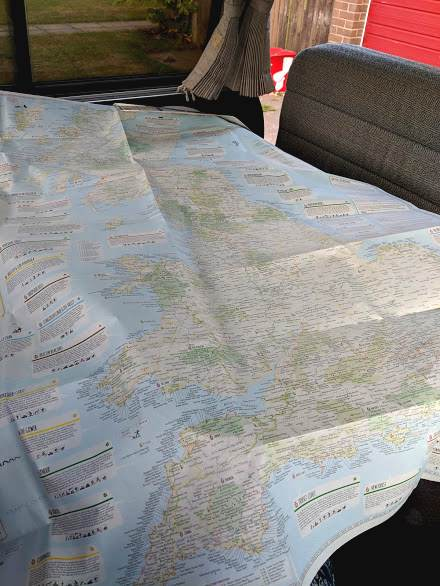 Image of fully opened paper map spread on table top in camper van
