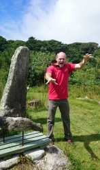 Image of man in red T-shirt and brown trousers pretending to be a zombie with collar and chain around neck attached to standing stone