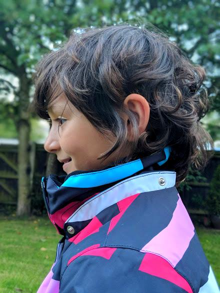 Image of profile view of dark haired child wearing white, black, blue and pink winter jacket showing high neck at back