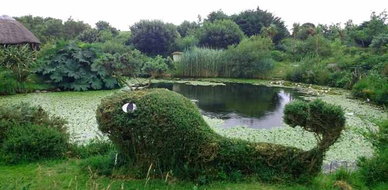 Image of whale shaped topiary in front of lake with vegetation all around