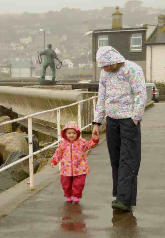 Image of woman in navy and white waterproofs holding hand of smiling toddler in red and pink waterproofs walking along wet pavement with stone houses and fisherman statue behind