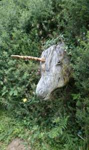 Image of wooden unicorn's head sticking out of leafy bushes