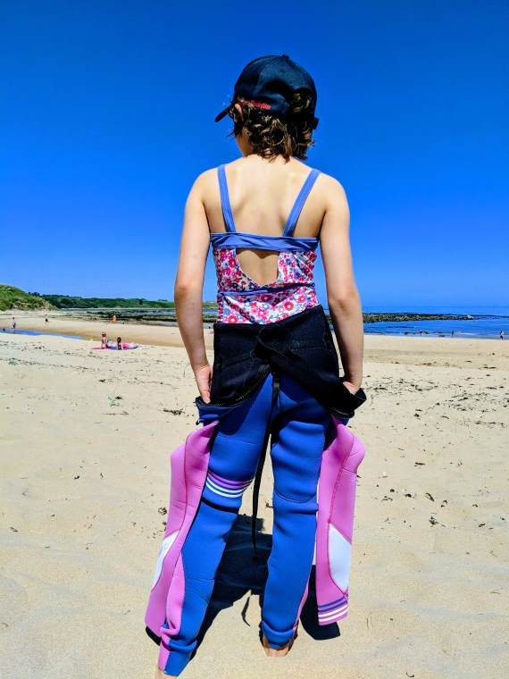 Image Of Girl In Navy Cap With Back To Camera Wearing Pink And Blue Swimsuit Under Pink And Blue Wetsuit With Beach, Sea And Blue Sky