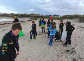 Image of adult with group of children carrying litter picking grabbers and wearing green scout uniform on beach searching the ground