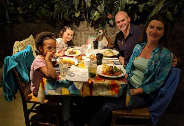 Image of family of 4 sitting at a table laden with food in front of a wall of jungle greenery