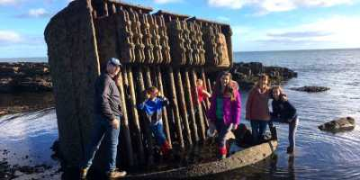 Image of family standing on large rusting metal object in sea with rocks and seaweed around