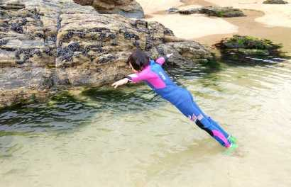 Image of girl in blue and pink wetsuit doing trust fall into shallow sandy rockpool on beach