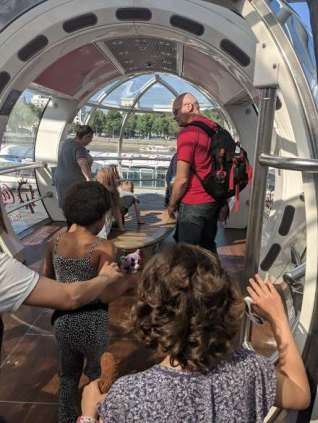 Image of group of people getting into glass capsule on millennium wheel overlooking river with trees in background