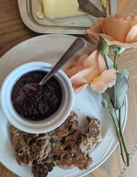 Image of plate of browned cakes with white ramekin of jam and spoon, peach coloured rose stem and pat of butter