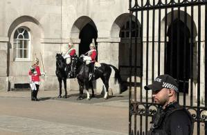 Image of policeman in black uniform standing in front of metal gates behind which two mounted soldiers of the Household Cavalry stand with soldier on foot